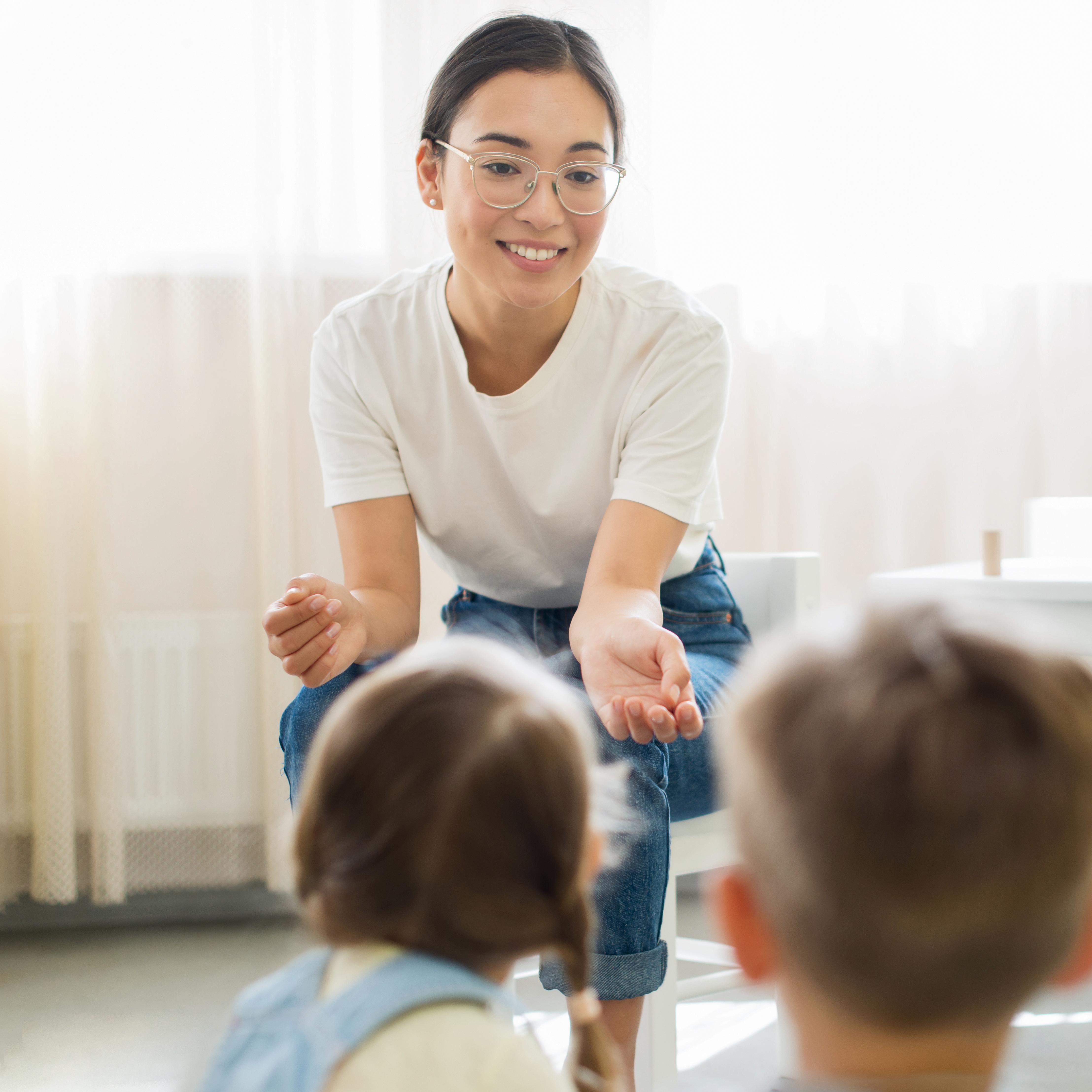 kindergarten-teacher-explaining-something-to-her-students